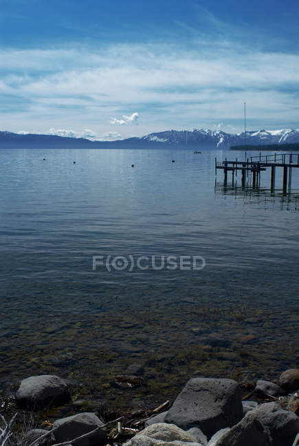 Rocks along lake shoreline with jetty — Stock Photo