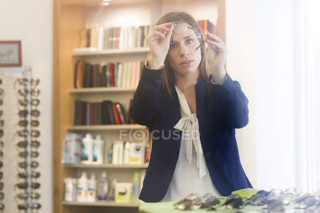 Woman in opticians looking at pair of glasses — Stock Photo