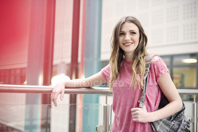 Молодая женщина смотрит в сторону, улыбаясь в городе — стоковое фото