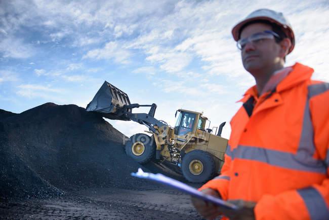 Travailleur dans une station de chargement de charbon avec pelleteuse et pile de charbon à la mine de charbon à ciel ouvert — Photo de stock