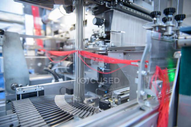 Red yarn passing through threading machine — Stock Photo