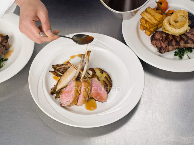 Person hand drizzling gravy on lamb — Stock Photo