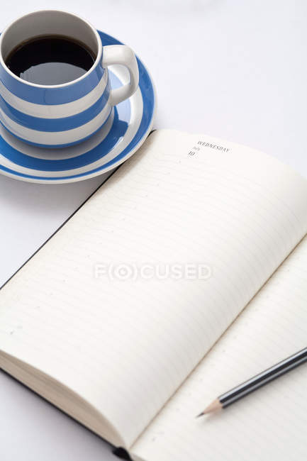 Coffee and open diary on table — Stock Photo