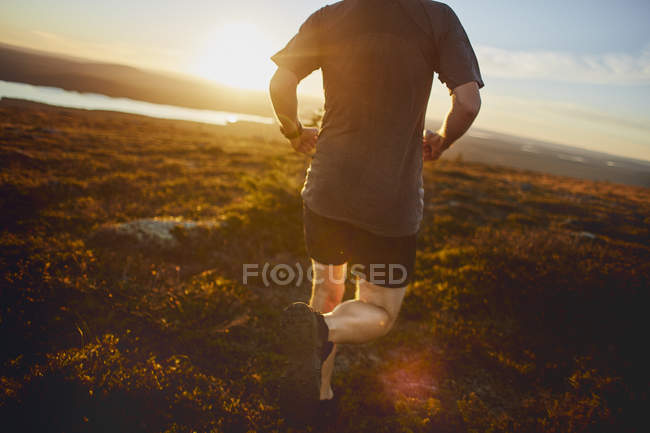 Cropped shot of mature athlete running in rural landscape — Stock Photo