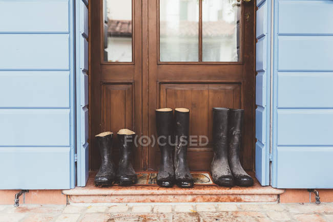 Three pairs of rubber boots on doorstep — Stock Photo
