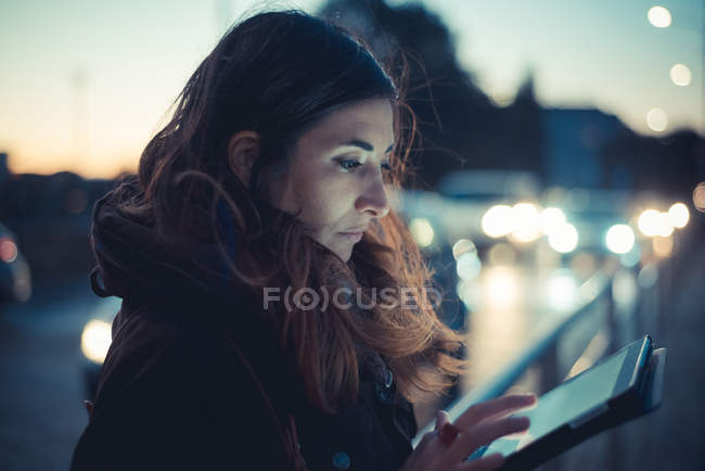 Mid adult woman using digital tablet touchscreen on street at dusk — Stock Photo