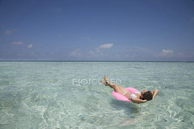 Mid adult woman on rubber ring in Indian Ocean, Maldives — Stock Photo
