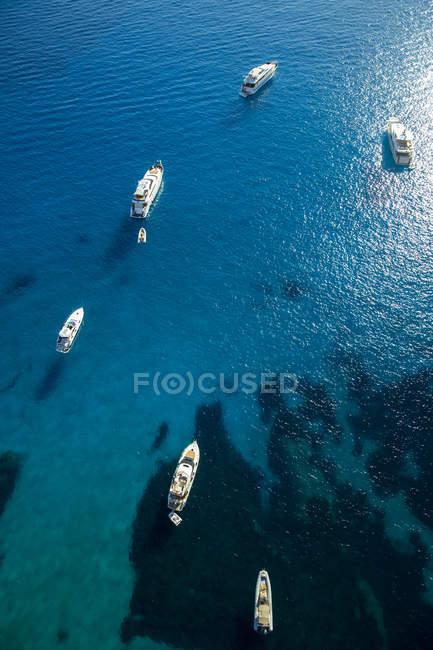 Воздушный вид яхт, стоящих на якоре в морской воде при солнечном свете — стоковое фото