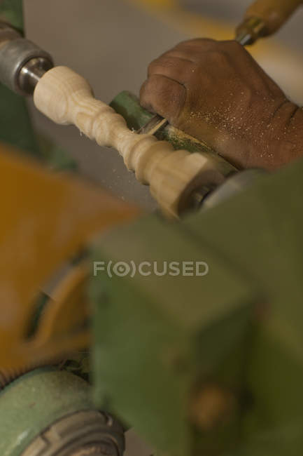 Close up of carpenter turning wood with chisel in workshop — Stock Photo