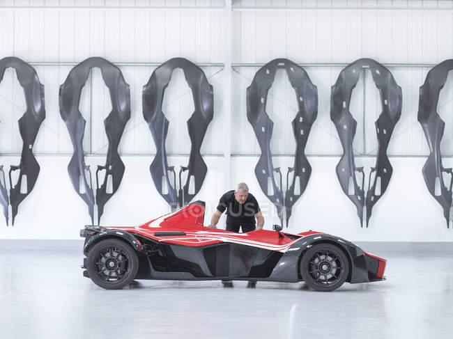 Ingenieur inspiziert Supersportwagen in Fabrik mit Carbon Fibre Auto Karosserien an Wand — Stockfoto