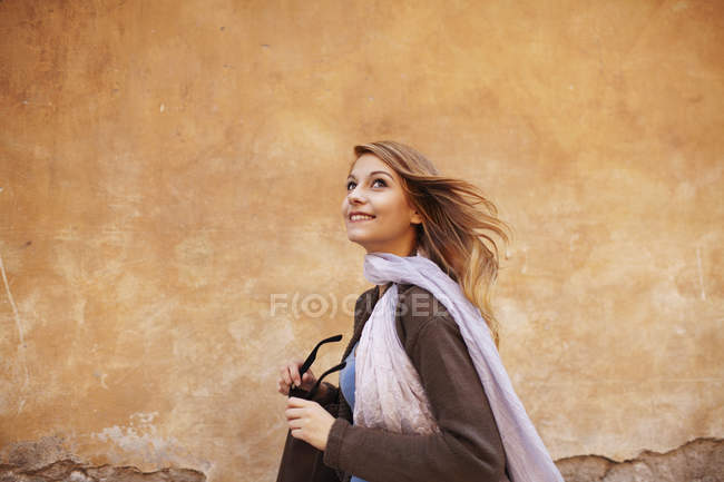 Young woman strolling down street looking sideways — Stock Photo