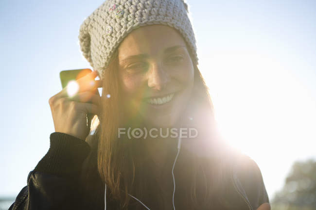 Portrait of young woman wearing earphones listening to music — Stock Photo