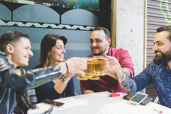 Group of friends toasting at outdoor cafe together — Stock Photo