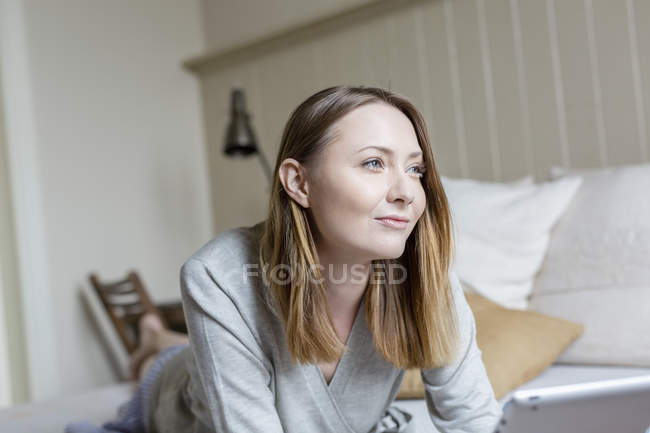 Portrait of woman lying on front on bed looking away smiling — Stock Photo