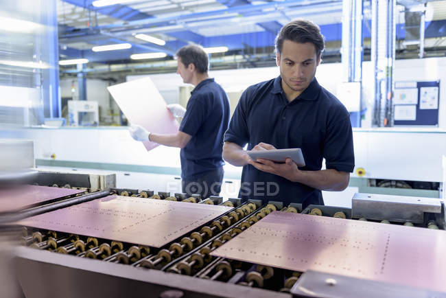 Workers inspecting circuit board during manufacture in circuit board factory — Stock Photo