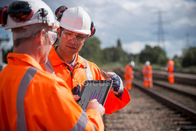 Railway workers using digital tablet to discuss work — Stock Photo