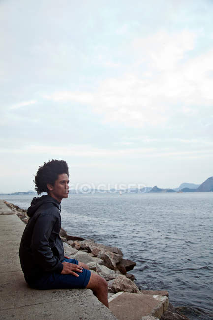Young man sitting on wall looking at sea, Rio de Janeiro, Brazil — Stock Photo
