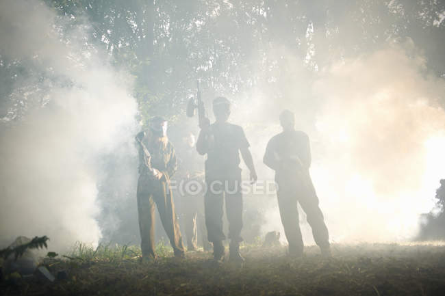 Paintball players in action standing in smoke cloud — Stock Photo