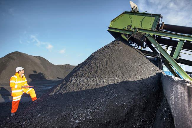 Travailleur inspectant la machine à charbon par pile de charbon à la mine de charbon à ciel ouvert — Photo de stock