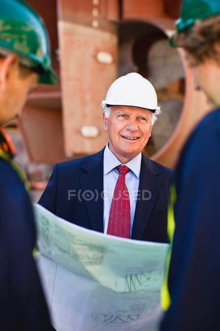 Les travailleurs lisent les plans sur la cale sèche — Photo de stock