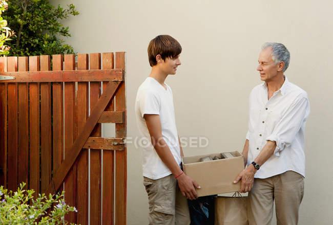 Pai e filho carregando caixa juntos — Fotografia de Stock