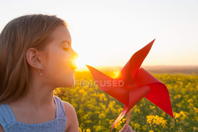 Girl playing with pinwheel outdoors — Stock Photo