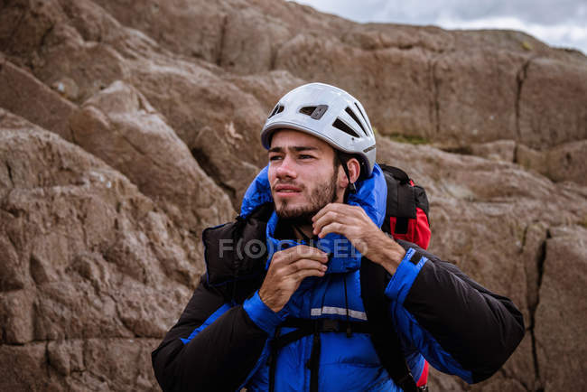 Joven escalador masculino en casco de sujeción de roca, The Lake District, Cumbria, Reino Unido - foto de stock