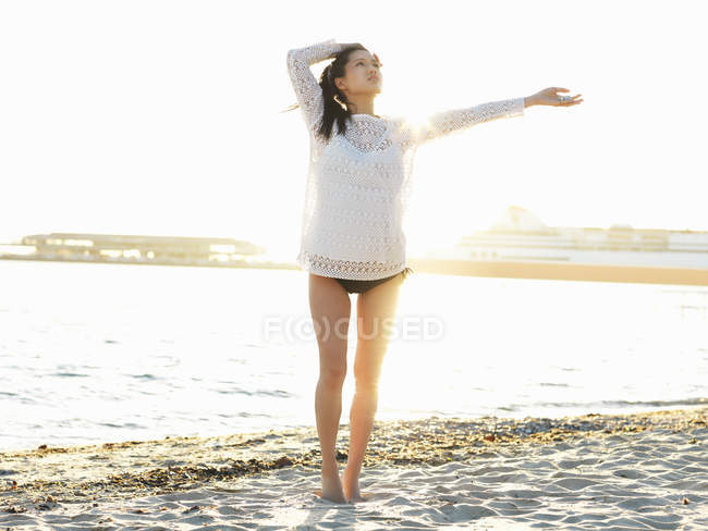 Young woman on sunlit beach with arm out, Port Melbourne, Melbourne, Victoria, Australia — Stock Photo