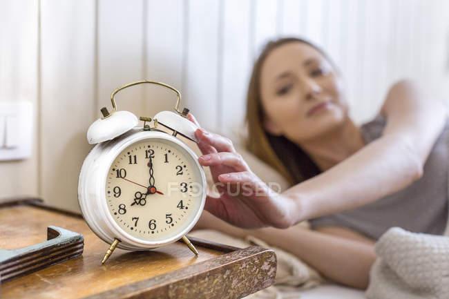 Mulher na cama, atingindo para despertador na mesa de cabeceira — Fotografia de Stock
