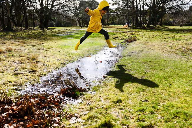 Boy in yellow anorak jumping over puddle in park — Stock Photo