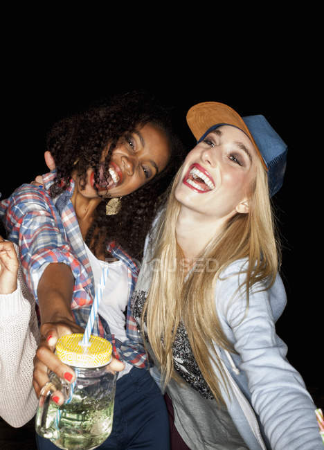 Young women huddled together holding mason jars open mouthed smiling — Stock Photo