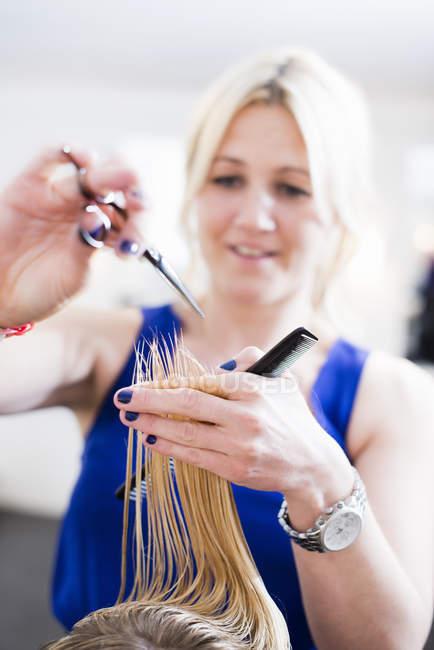 Cabeleireiro corte cabelo cliente feminino no salão — Fotografia de Stock