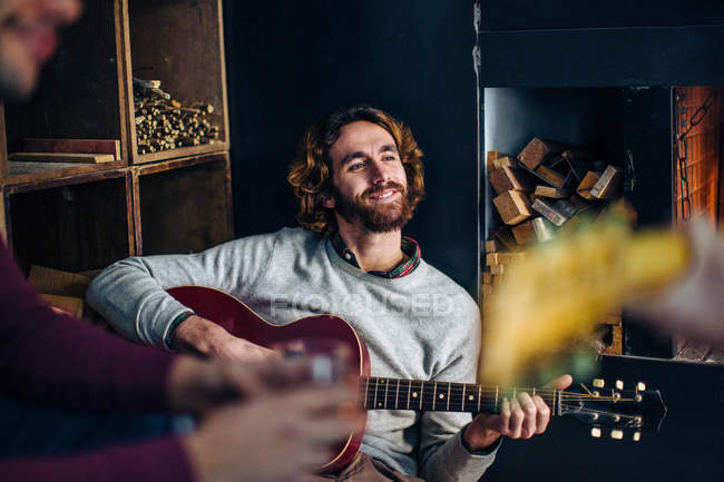 Young man sitting on floor playing guitars in living room — Stock Photo