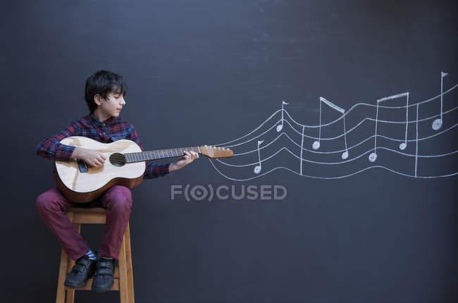 Ragazzo che suona la chitarra davanti alla parete della lavagna con la notazione musicale — Foto stock