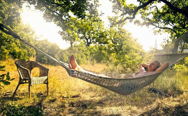 Людина розслабляючий в гамаку на відкритому повітрі — стокове фото