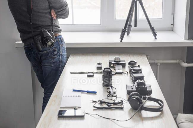 Male photographer next to photography equipment on studio desk — Stock Photo