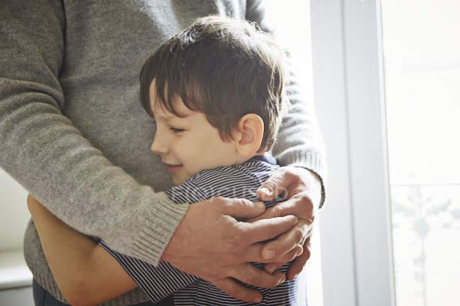 Vater und Sohn umarmen sich am Fenster, beschnitten — Stockfoto