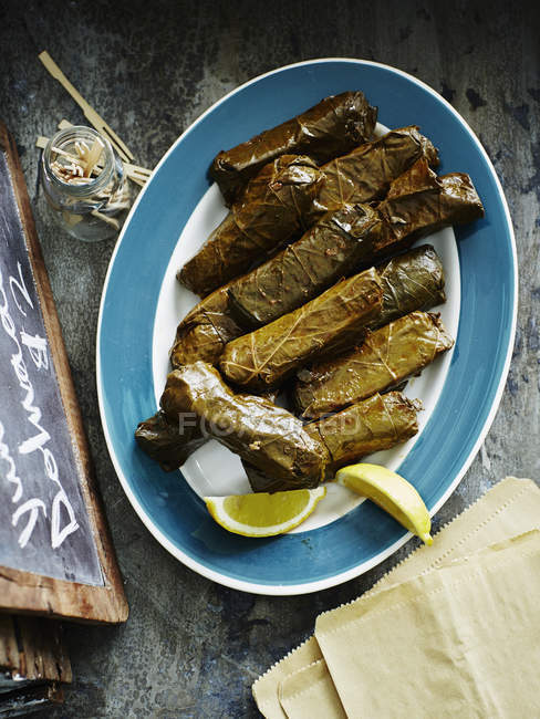 Dolmades with lemon slices on plate, top  view — Stock Photo