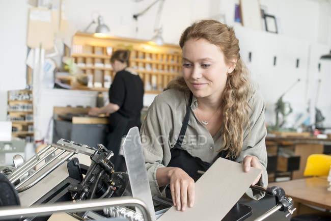 Imprimante femelle insérer le papier à la machine en atelier — Photo de stock