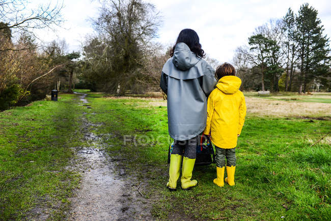 Rear view of woman with son in yellow anorak standing in park — Stock Photo
