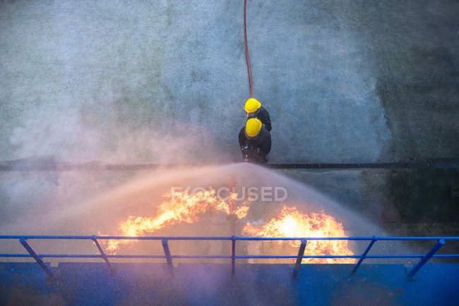 Two firefighters putting out fire in fire simulation training facility, overhead view — Stock Photo