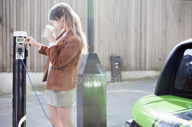 Жінка зарядки електричний автомобіль на вулиці — стокове фото