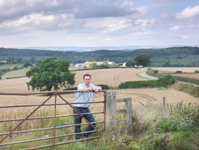 Farmer with crops and farm — Stock Photo