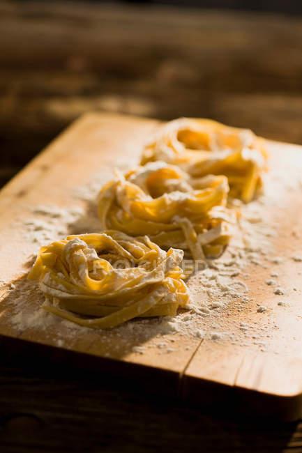 Ungekochte Nudeln auf Holzbrett mit Mehl — Stockfoto