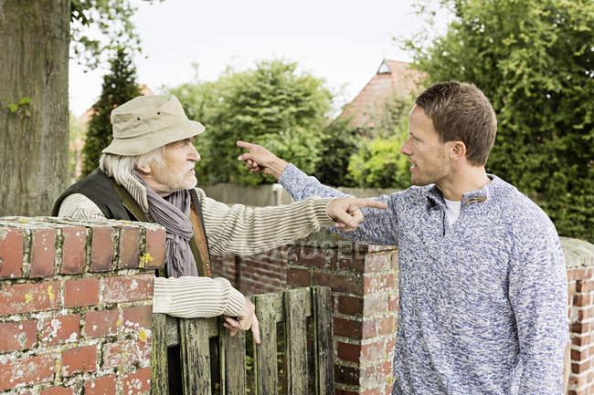Старший мужчина и середине взрослый человек утверждая — стоковое фото