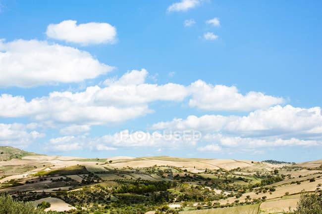 Paisagem azul nublada de céu e campos na luz solar — Fotografia de Stock