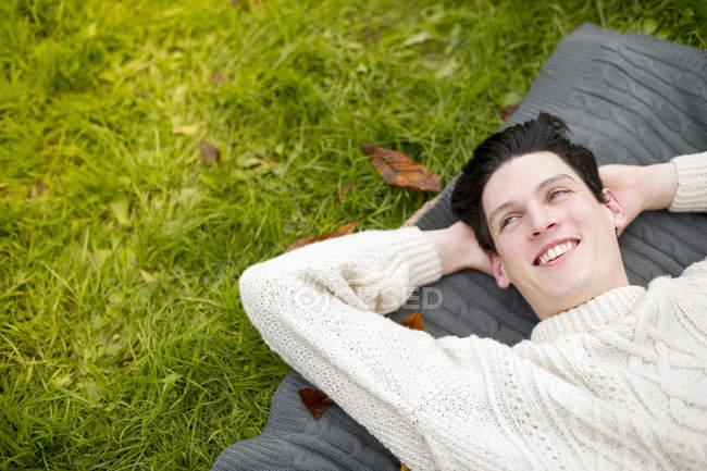 Hombre joven acostado en la alfombra con suéter - foto de stock
