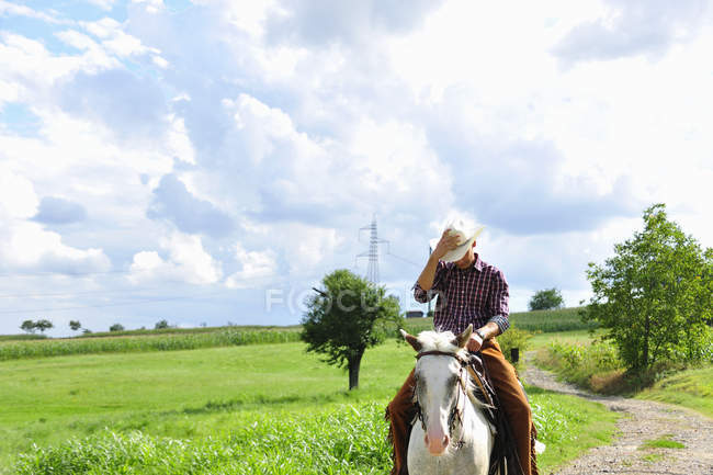 Young man adjusting cowboy hat riding horse on rural road — Stock Photo