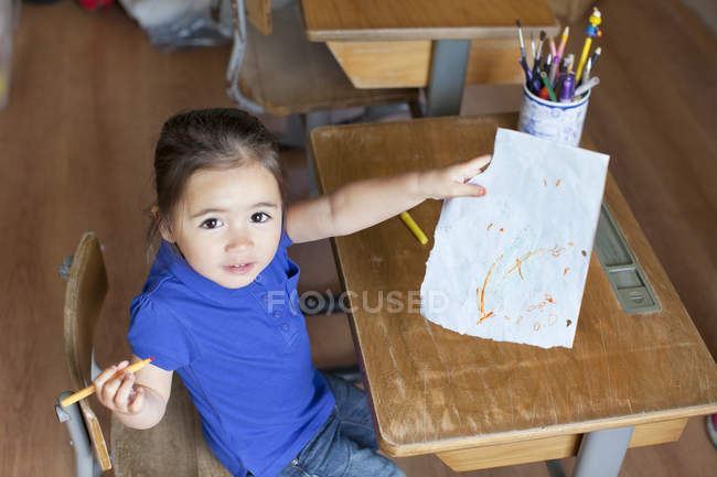 Girl at desk showing picture, high angle view — Stock Photo