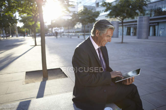 Businessman sitting outside and using digital tablet — Stock Photo